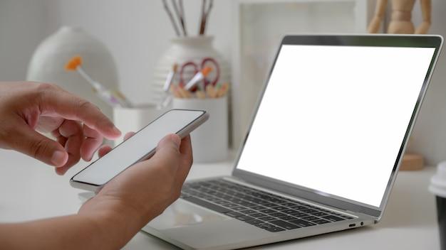 Przycięte Ujęcie Artysty Za Pomocą Pustego Ekranu Smartfona Z Pracą Z Pustym Ekranem Laptopa I Narzędziami Do Malowania Premium Zdjęcia