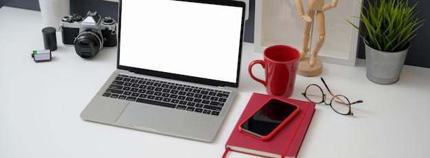 Przycięte Ujęcie Biurka Z Makietą Laptopa, Smartfona I Materiałów Biurowych Premium Zdjęcia