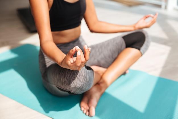 Przycięte Ujęcie Fitness Kobieta Siedzi W Pozycji Lotosu Darmowe Zdjęcia