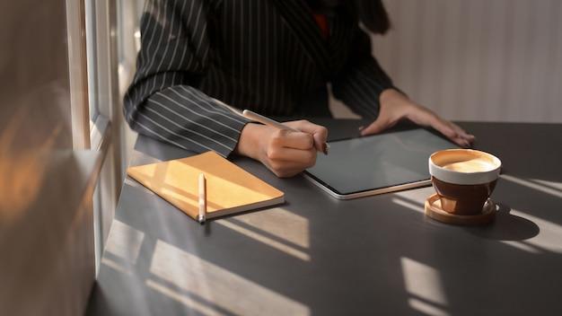 Przycięte Ujęcie Kobiety Za Pomocą Cyfrowego Tabletu W Wygodnym Miejscu Pracy Premium Zdjęcia