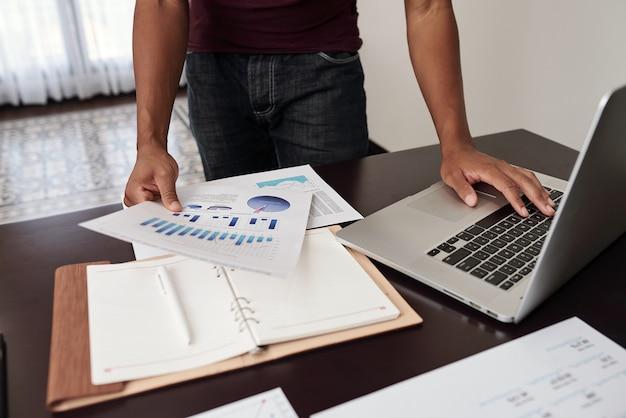 Przycięte Zdjęcie Analityka Finansowego Sprawdzającego Raporty Z Wykresami I Diagramami Na Biurku Premium Zdjęcia