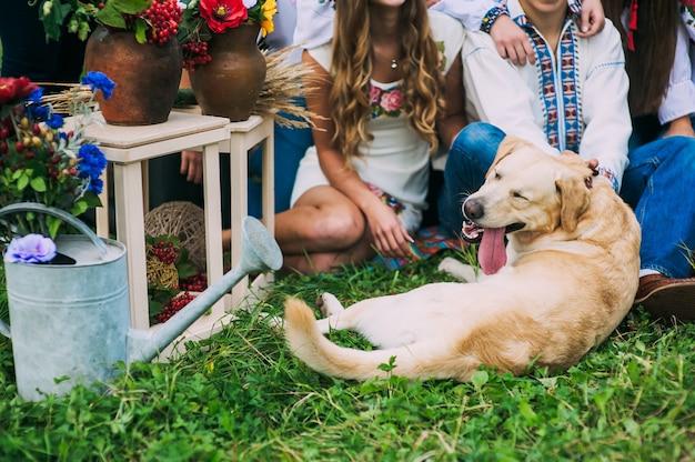 Przycięte Zdjęcie Portret Jasnowłosego Psa Z Wystającym Językiem W Pobliżu Osób Sfotografowanych W Wiejskim Wystroju W Stylu Ukraińskim. Jasne Kolory, Stonowany Obraz. Premium Zdjęcia