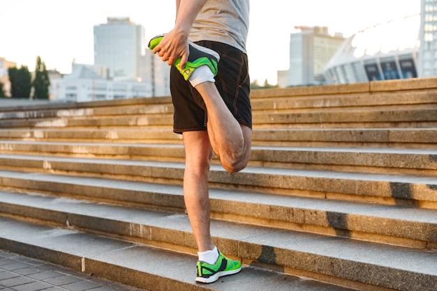 Przycięte Zdjęcie Sportowca Rozciągającego Nogi Premium Zdjęcia