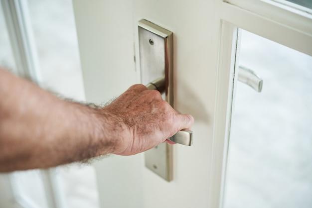 Przycięty Anonimowy Mężczyzna Trzyma Klamkę, Aby Otworzyć Drzwi Darmowe Zdjęcia