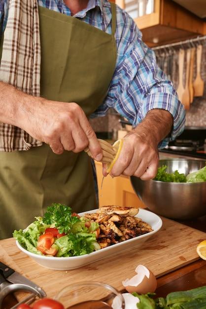 Przycięty mężczyzna kucharz, dodając sok z cytryny do naczynia Darmowe Zdjęcia