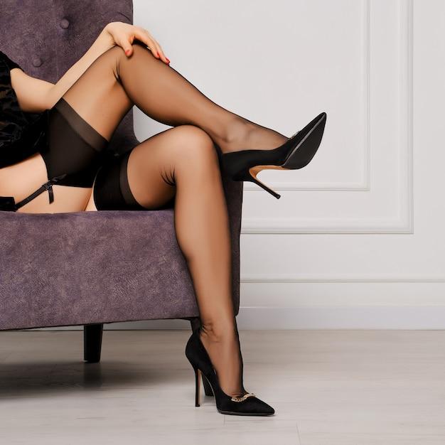 Przycięty Obraz Kobiecych Nóg W Pończochach I Pas Do Pończoch, Siedząc W Fotelu Premium Zdjęcia
