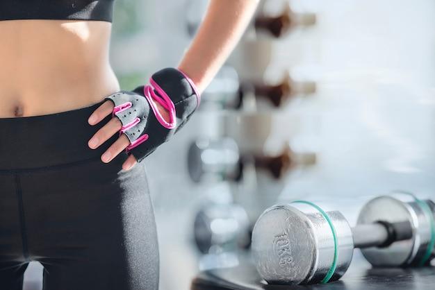Przycięty obraz treningu kobieta ćwiczenia w siłowni fitness z hantle Premium Zdjęcia