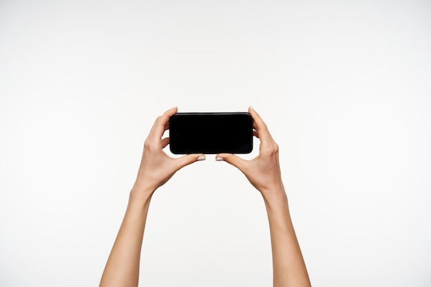 Przycięty Portret Uniesionych Jasnoskórych Ramion Kobiety Trzymającej Telefon Komórkowy Poziomo Podczas Oglądania Wideo Na Nim, Stojąc Na Białym Darmowe Zdjęcia