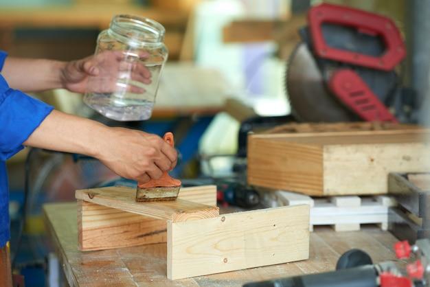 Przycięty stolarz polerujący drewno na stole warsztatowym Darmowe Zdjęcia