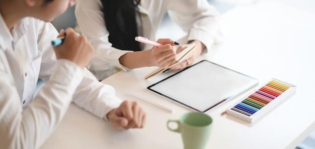 Przycięty Strzał Młodego Zespołu Projektantów, Który Wymienia Koncepcje Pomysłów, Jednocześnie Używając Makiety Tabletu W Nowoczesnym Biurze Premium Zdjęcia