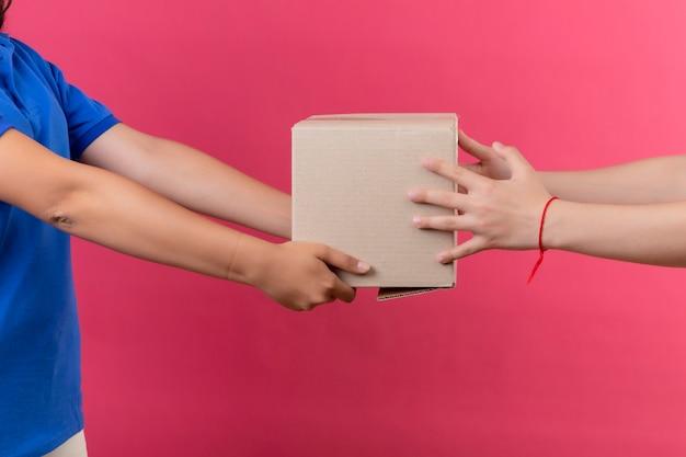 Przycięty Widok Dziewczyny Dostawy, Która Daje Klientowi Pakiet Pudełkowy Na Odizolowanej Różowej Przestrzeni Darmowe Zdjęcia