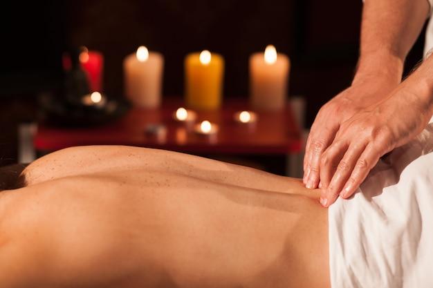 Przycięty z bliska rąk wykwalifikowanego masażysty pracującego z jego klientem. fachowy masażysta masuje plecy kobieta przy zdrojem, świeczki pali na tle, kopii przestrzeń. wypoczynek, wellness Premium Zdjęcia