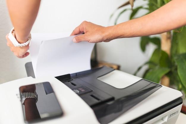 Przycinaj Ręce, Dotykając Papieru W Drukarce Premium Zdjęcia