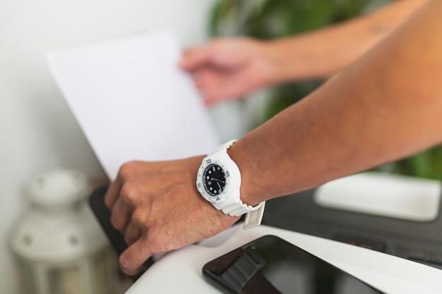 Przycinaj Ręce, Kładąc Papier W Drukarce Premium Zdjęcia