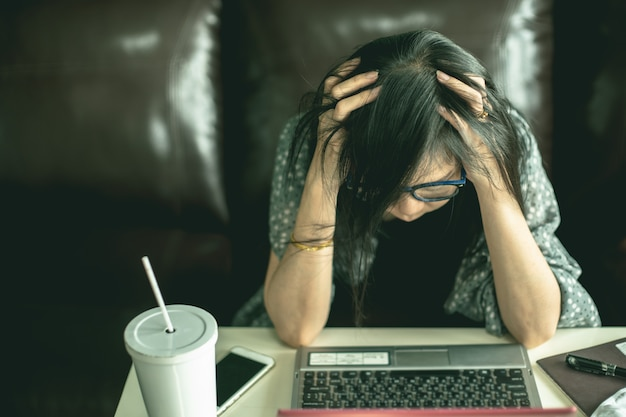 Przygnębiona Azjatycka Kobieta Siedzi Przy Biurkiem W Domu. Premium Zdjęcia