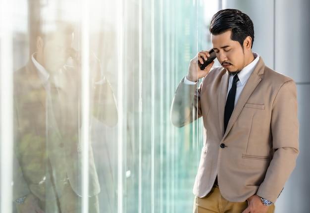 Przygnębiony Biznesowy Mężczyzna Opowiada Na Smartphone W Biurze Premium Zdjęcia
