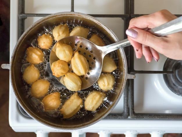 Przygotowanie Arabskiego Deseru Tulumba We Wrzącym Oleju. Tulumba - Smażony Miód Z Gąbki W Syropie Arabskim. Premium Zdjęcia