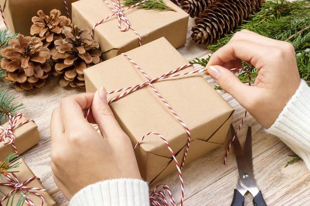 Przygotowanie świątecznych prezentów. pudełko prezentowe owinięte czarno-białym pasiastym papierem, skrzynią pełną szyszek sosny i świątecznych zabawek i materiałów do pakowania na białym tle starego drewna Premium Zdjęcia