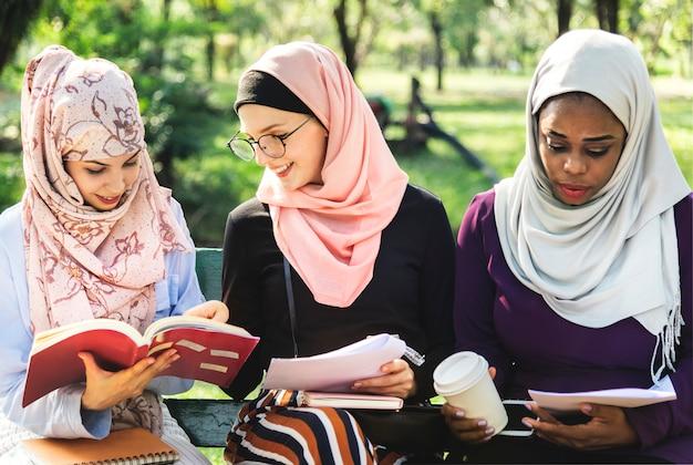 Przyjaciele czyta książkę wpólnie przy parkiem Premium Zdjęcia