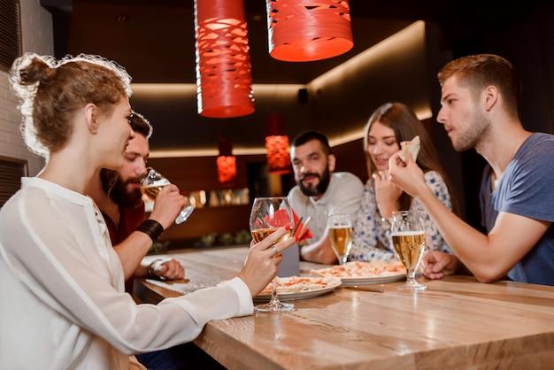 Przyjaciele jedzący pizzę i pijący piwo w pizzerii. Premium Zdjęcia