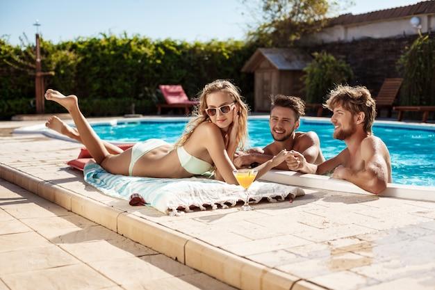 Przyjaciele Mówią, Uśmiechają Się, Piją Koktajle, Odpoczywają, Relaksują Się W Pobliżu Basenu Darmowe Zdjęcia