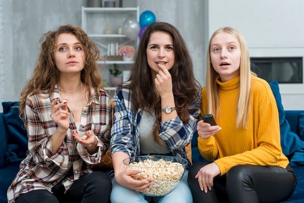 Przyjaciele oglądający film podczas jedzenia popcornu Darmowe Zdjęcia