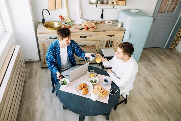 Przyjaciele opiekania soku i filiżanki kawy w kuchni Darmowe Zdjęcia
