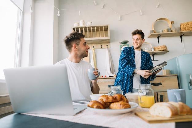 Przyjaciele patrząc na siebie trzymając magazyn i filiżankę kawy w kuchni Darmowe Zdjęcia