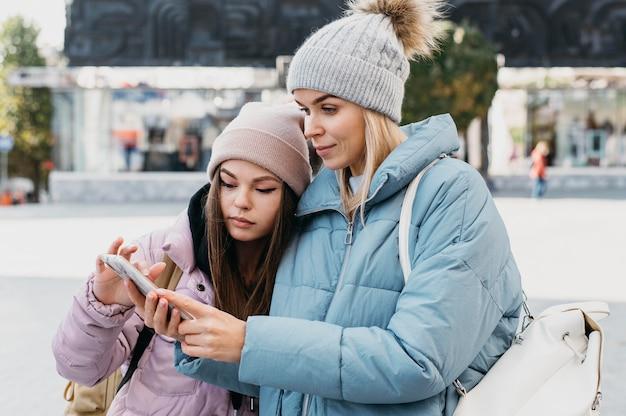 Przyjaciele Patrząc Na Telefon Na Zewnątrz W Zimie Darmowe Zdjęcia