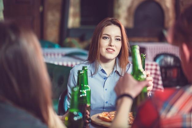Przyjaciele Piją Drinki W Barze, Siedzą Przy Drewnianym Stole Z Piwem I Pizzą. Skoncentruj Się Na Pięknej Dziewczynie Dotykającej Jej Butelki. Premium Zdjęcia