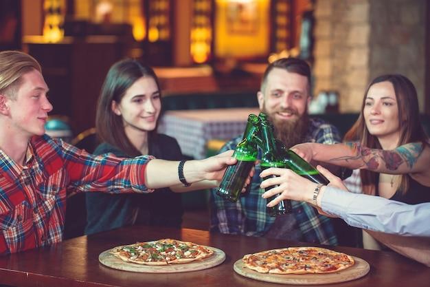 Przyjaciele Piją Drinki W Barze, Siedzą Przy Drewnianym Stole Z Piwem I Pizzą. Premium Zdjęcia