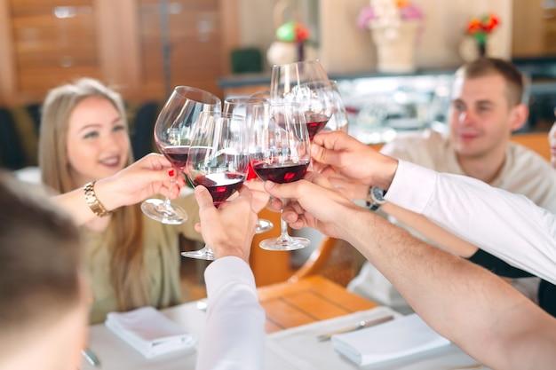 Przyjaciele piją wino na tarasie restauracji. Premium Zdjęcia