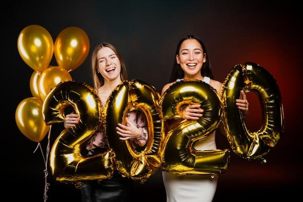 Przyjaciele pozuje z złotymi balonami przy nowym rokiem bawją się Darmowe Zdjęcia