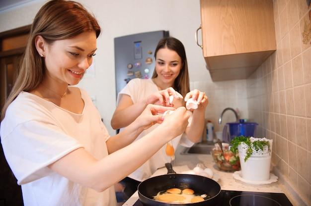 Przyjaciele Przygotowują Brekfast I Jedzą Razem W Kuchni. Premium Zdjęcia