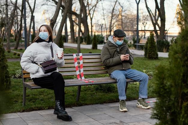 Przyjaciele Siedzący Na Odległość I Noszący Maskę Darmowe Zdjęcia