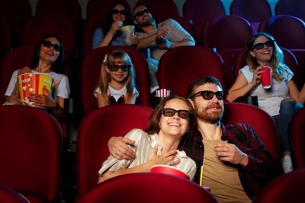 Przyjaciele siedzący w kinie oglądają film jedzący popcorn i wodę pitną. Premium Zdjęcia