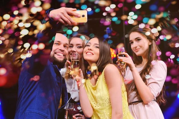 Przyjaciele świętują wydarzenie, śmiejąc się, tańcząc i pijąc szampana Premium Zdjęcia
