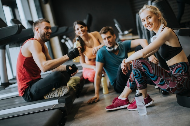 Przyjaciele w sportowej rozmawiają razem stojąc w siłowni po treningu Premium Zdjęcia