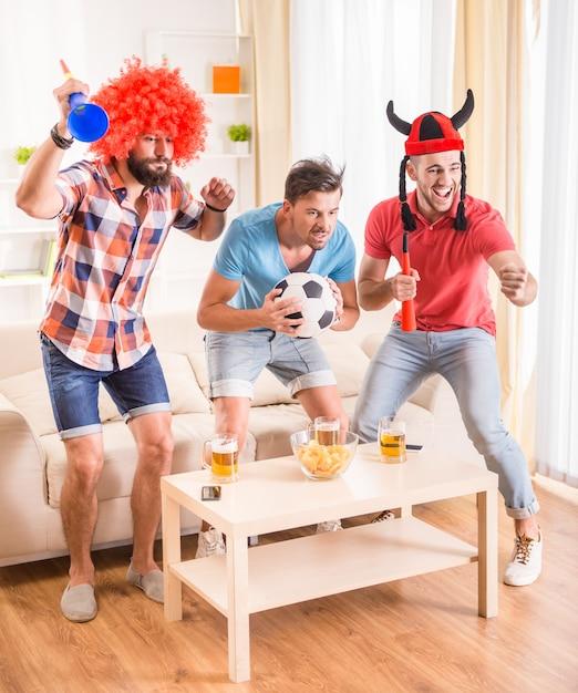 Przyjaciele w strojach piłkarskich emocjonalnie oglądają piłkę nożną. Premium Zdjęcia