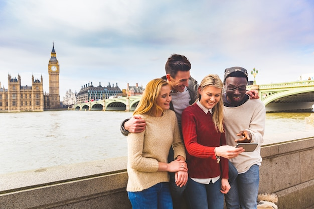 Przyjaciele zabawy z smartphone w big ben w londynie Premium Zdjęcia