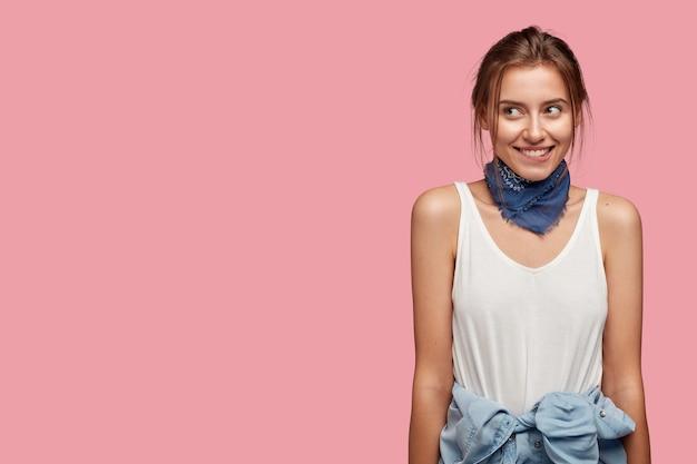 Przyjazna Młoda Kobieta W Okularach, Pozowanie Na Różowej ścianie Darmowe Zdjęcia