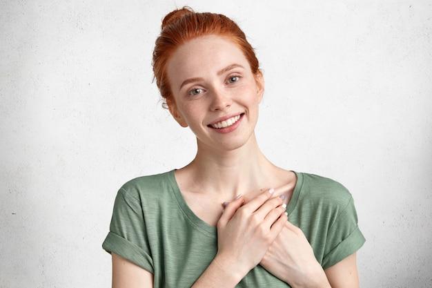 Przyjazna, Zadowolona śliczna Modelka Trzyma Ręce Na Sercu, Jest Komuś Wdzięczna, Wyraża Swoją życzliwość Lub Dobrą Wolę Na Białym Betonowym Murze. Darmowe Zdjęcia