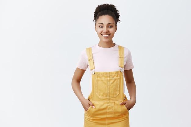 Przyjemna, śliczna, Ciemnoskóra Pracownica Pomagająca Klientom Znaleźć Odpowiedni Przedmiot Do Zakupu. Radosna, Przyjaźnie Wyglądająca Dziewczyna W Modnym żółtym Kombinezonie, Trzymająca Się Za Ręce W Kieszeniach I Uśmiechnięta Darmowe Zdjęcia