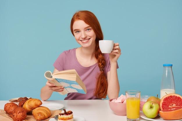 Przyjemnie Uśmiechnięta Rudowłosa Kobieta O Splecionych Włosach Siedząca Przy Stole Trzyma Białą Filiżankę Z Pysznym Napojem Darmowe Zdjęcia
