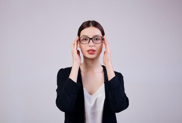 Przyjemnie Wyglądająca Kobieta Biznesu Stoi Na Szaro W Czarnej Kurtce, Koszulce I Okularach Komputerowych. Premium Zdjęcia