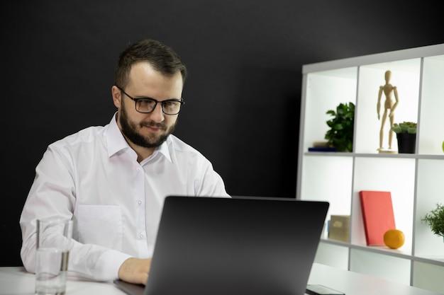 Przyjemny Biznesmen Surfujący Po Sieci W Przytulnym Biurowym Miejscu Pracy. Pracować W Domu Premium Zdjęcia