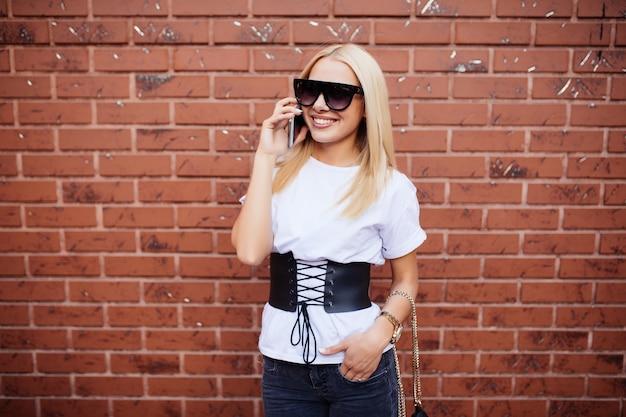 Przypadkowa Młoda Blondynka Rozmawia Przez Telefon Z Cegły Darmowe Zdjęcia
