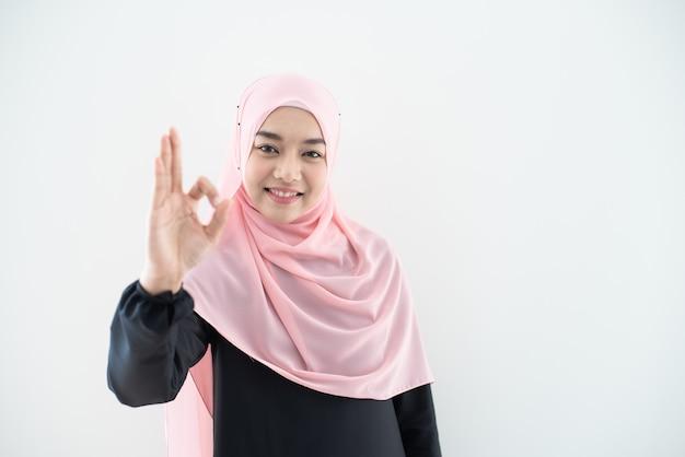 Przyrodni Długość Portret Azjatykcia Piękna Muzułmańska Młoda Kobieta Jest Ubranym Biznesowego Ubiór I Hijab Z Mieszanymi Pozami I Gestami Odizolowywającymi Na Szarości ścianie. Nadaje Się Do Technologii, Tematu Finansowania Biznesu. Premium Zdjęcia