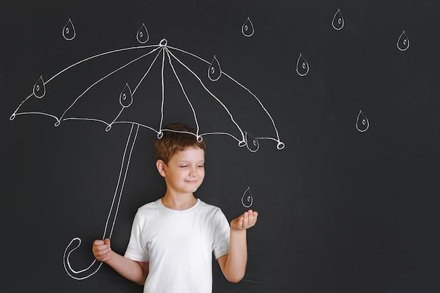 Przystojna Chłopiec Pod Kredowym Rysunkowym Parasolem Premium Zdjęcia