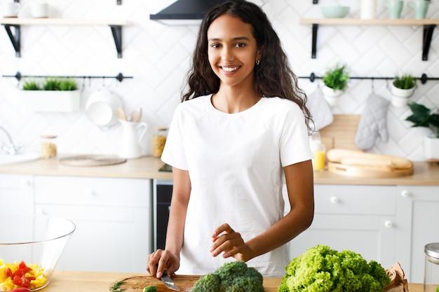 Przystojna Oliwkowa Kobieta Uśmiecha Się I Trzyma Nóż W Nowoczesnej Kuchni Ubrana W Białą Koszulkę, Przy Stole Ze świeżymi Warzywami Darmowe Zdjęcia